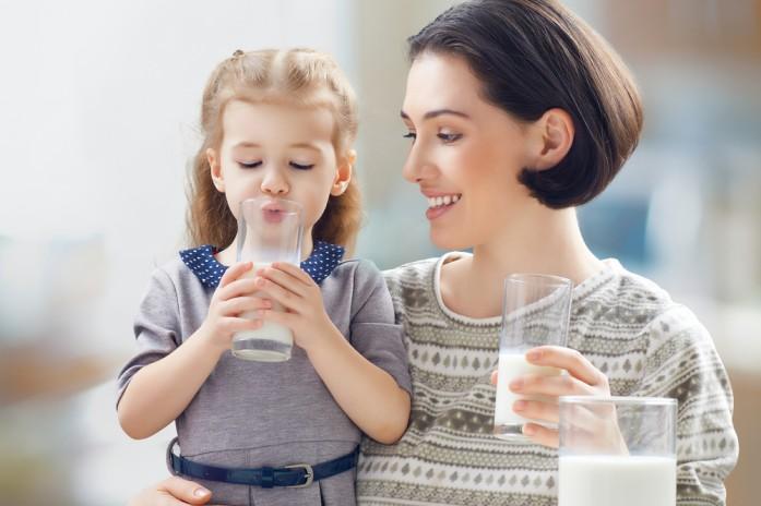 Дівчинка п'є молоко