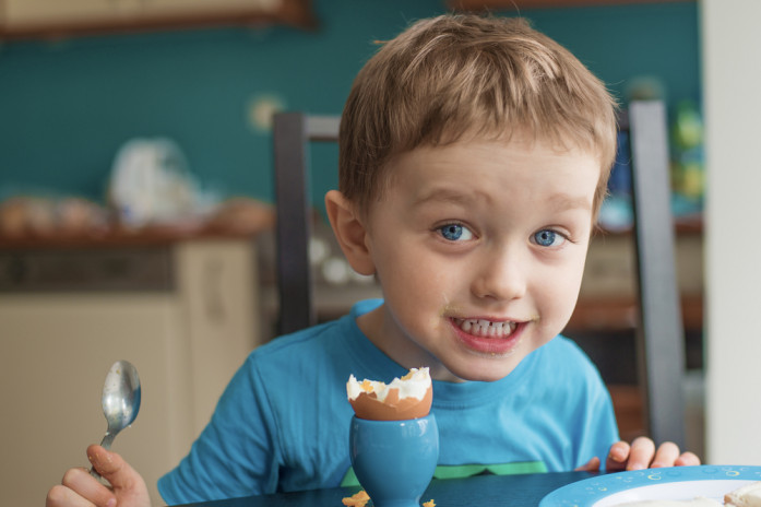 Мальчик ест яйцо при целиакии