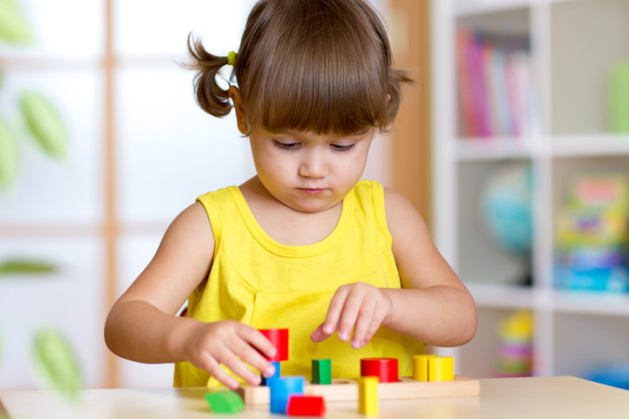 девочка изучает формы и цвета предметов