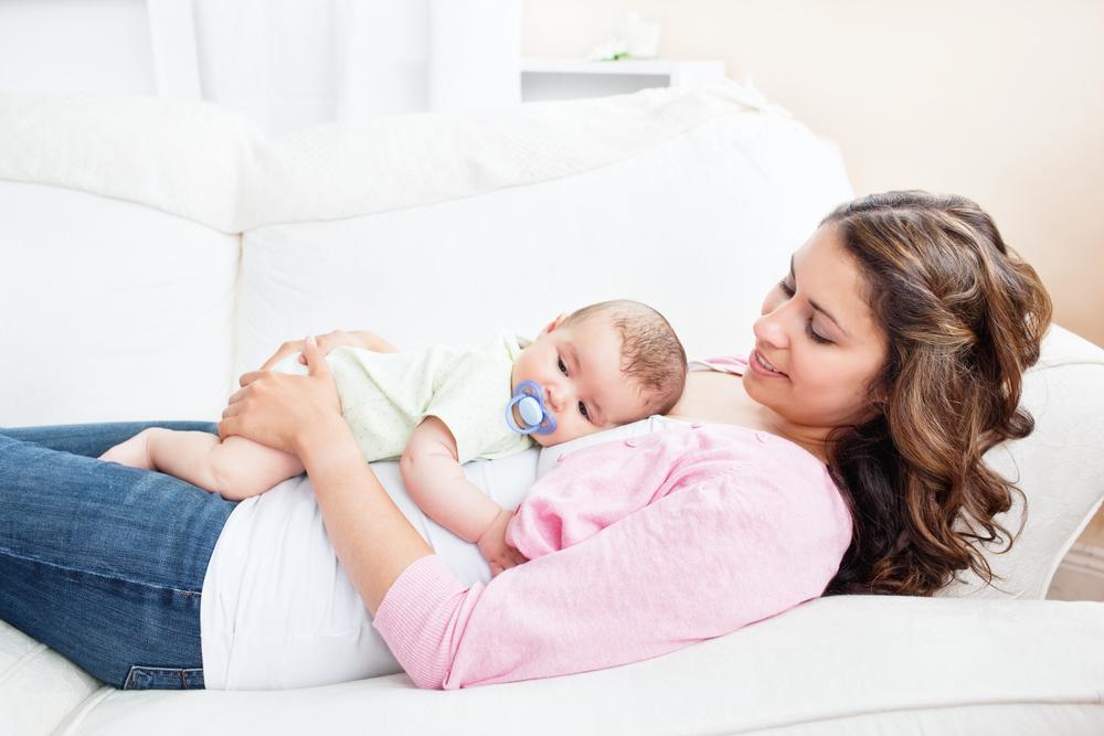 Мама с грудничком лежит на диване