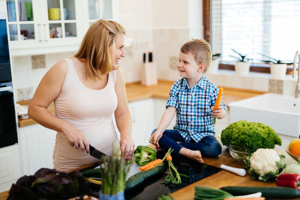 Беременная женщина с ребенком на кухне
