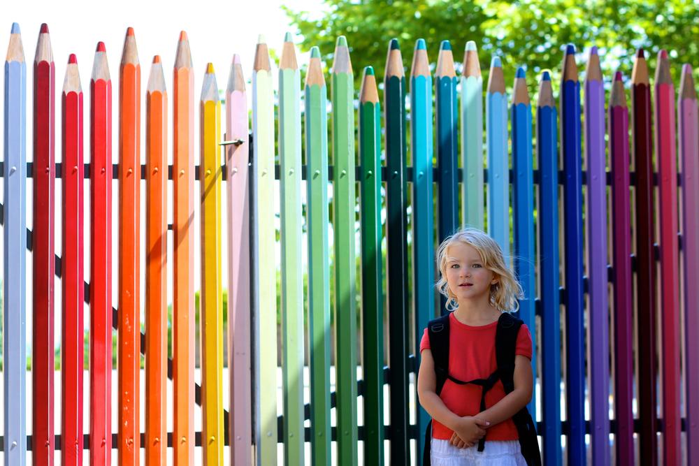 Девочка с ранцем на фоне цветного забора