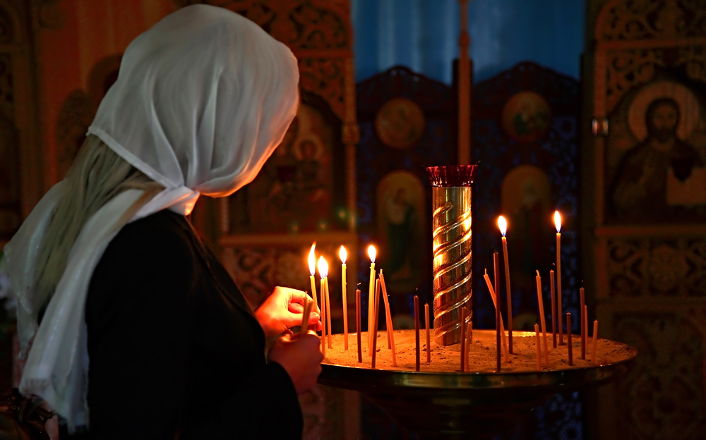 Девушка ставит свечи на Сретение Господне