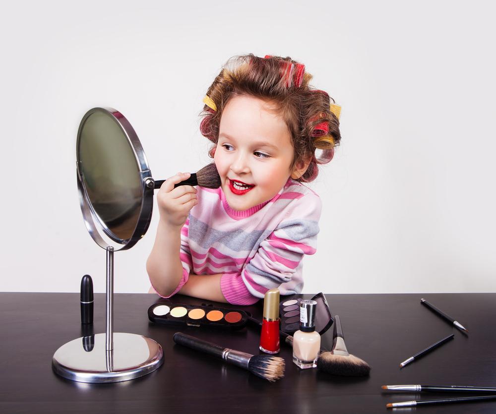 Маленькая девочка наносит макияж