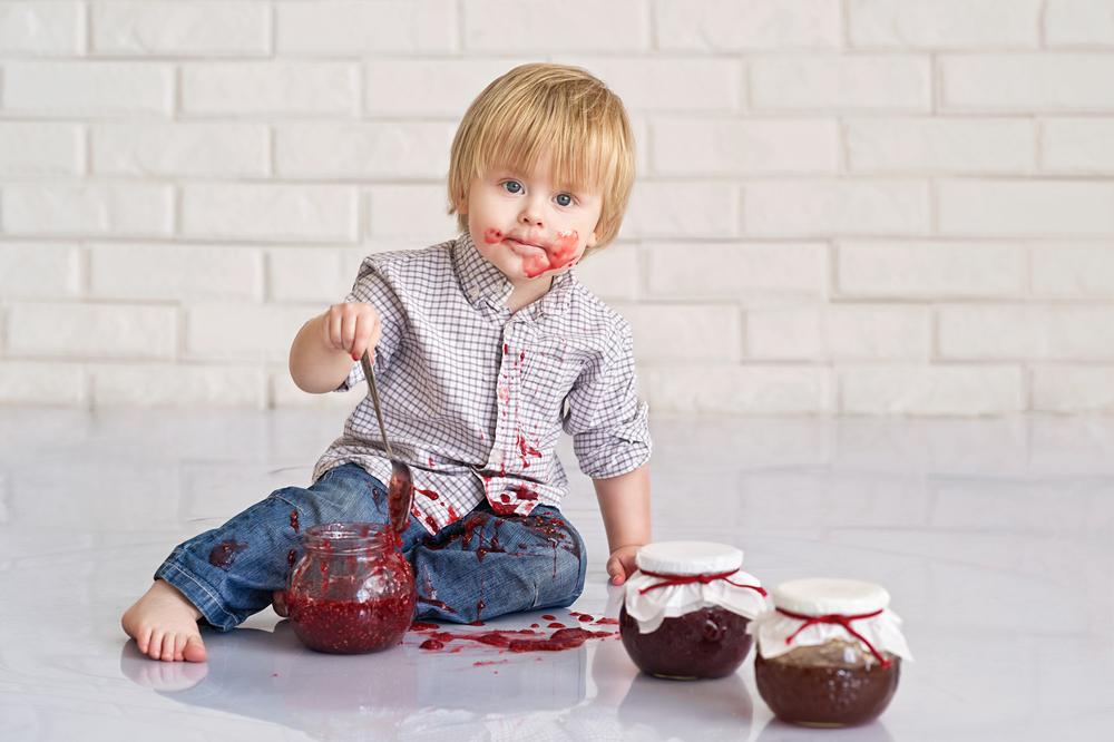 Ребенок ест ягодное варенье из крыжовника