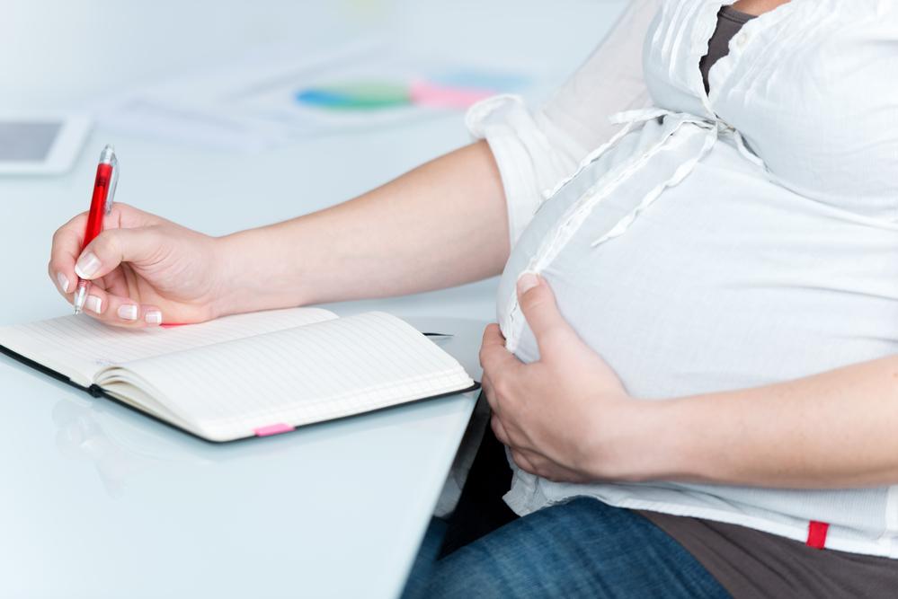 Беременная пишет ручкой - оформление декретного пособия