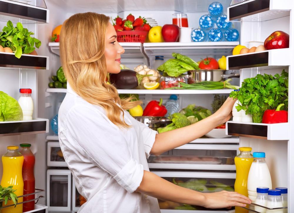 Жінка зберігає продукти в холодильнику