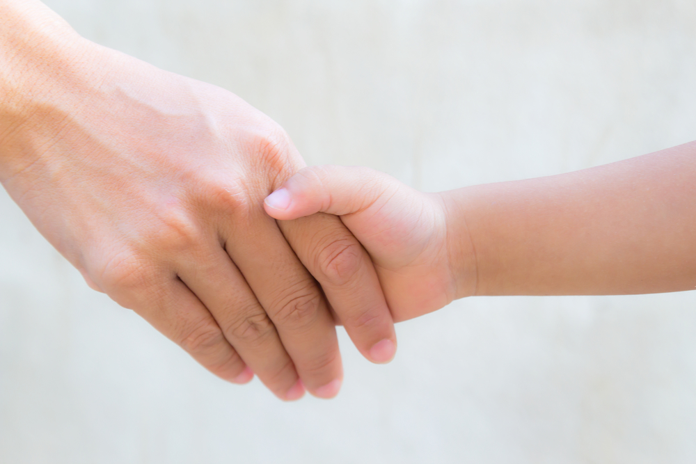 Мама тримає дитину за руку