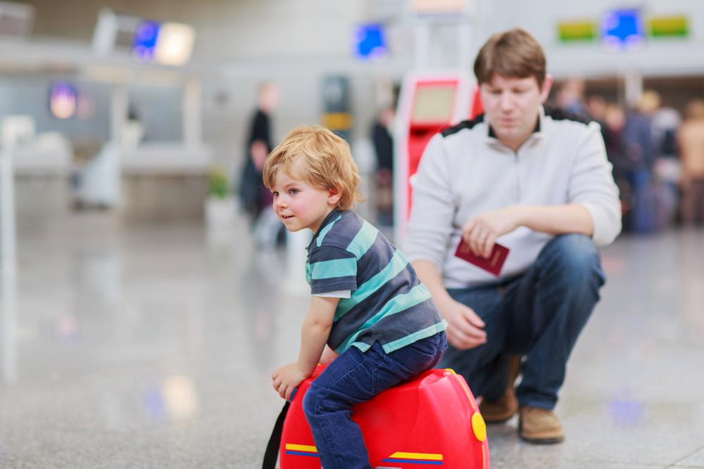 Ребенок сидит на чемодане в аэропорту