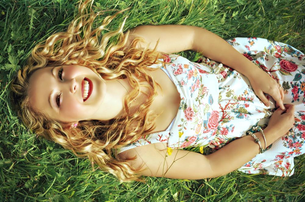Счастливая женщина в платье в цветочек на траве летом