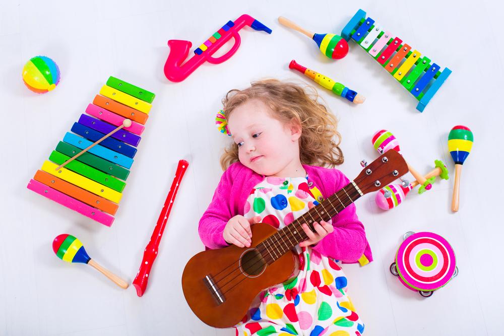 Девочка играет с музыкальными инструментами