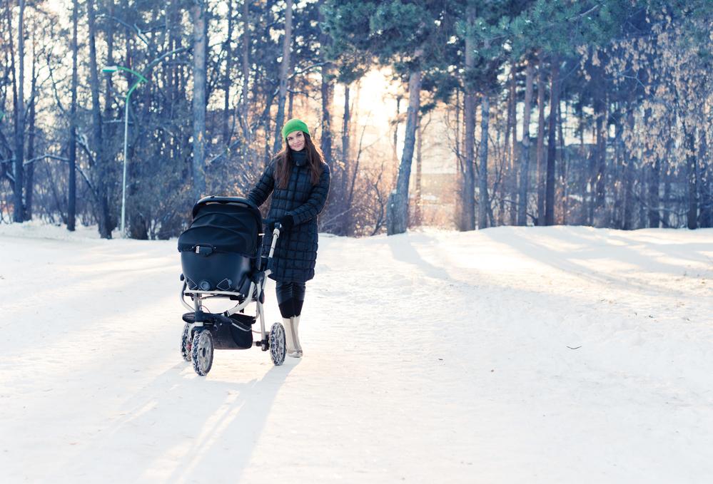 Мама с коляской дает ребенку витамин Д на солнце зимой