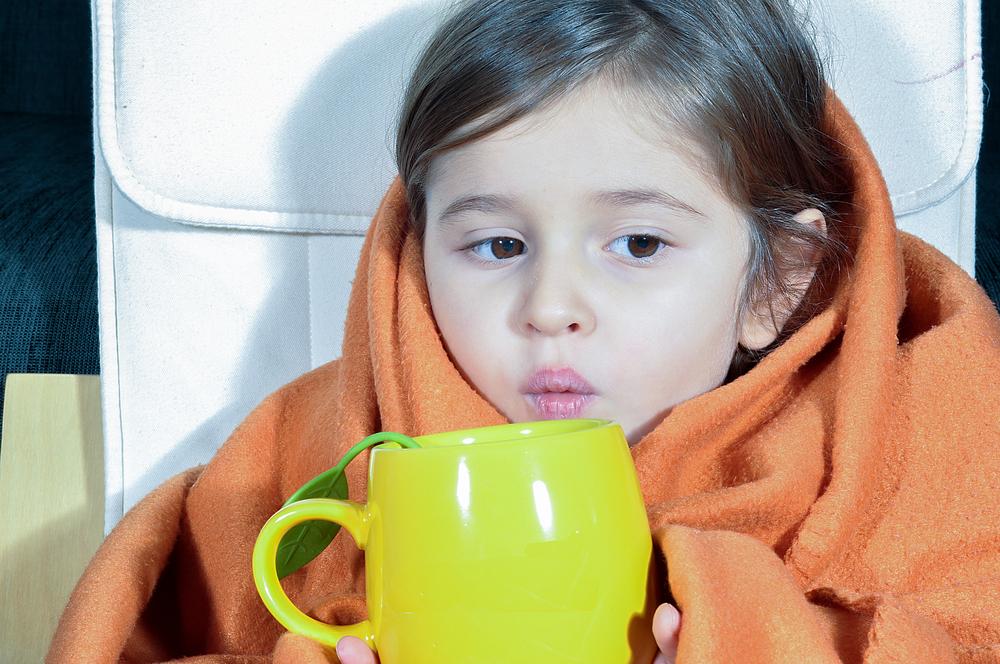 Дівчинка в ковдрі і з чашкою - кашель і ГРВІ