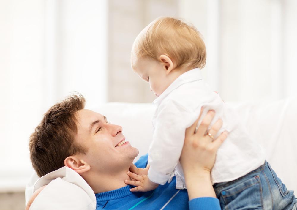 Папа играет с малышом на диване