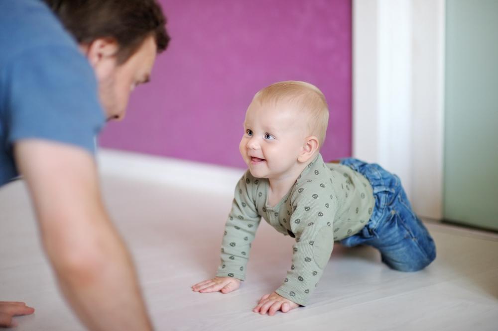 Папа играет с малышом на четвереньках